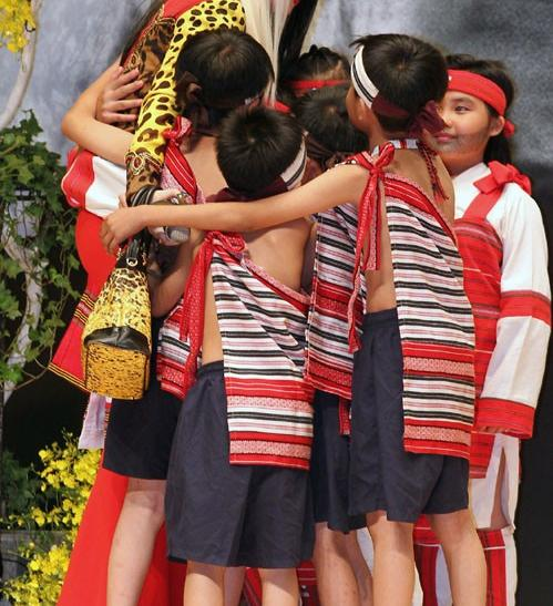 Lady Gaga hugs children from the traditional Taiwan aborigine Taiya tribe