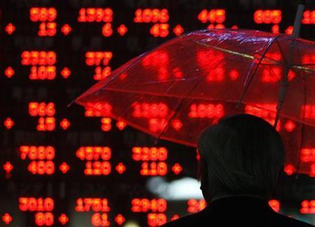 A businessman looks at share prices on an electronic board outside a brokerage in Tokyo