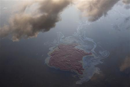 Clouds are reflected in water near a patch of oil from the Deepwater Horizon oil spill off Grand Terre Island, Louisiana