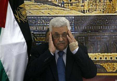 Palestinian President Mahmoud Abbas prays before the start of a meeting in Ramallah