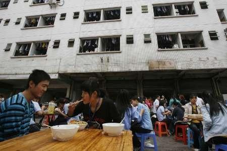 Migrant workers eat their lunch outside a dormitory building at a factory district in the southern Chinese city of Shenzhen in Guangdong province