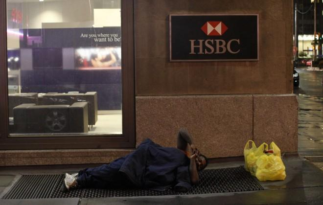 A homeless man sleeps on a street outside a branch of HSBC bank in New York