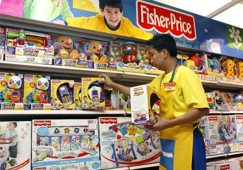 An employee arranges Fisher-Price toys at a store