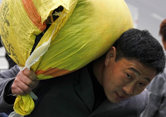 A migrant worker carries his belongings on his shoulder as he walks to a train station in Beijing October 19, 2010. China must lift the incomes and spending power of hundreds of millions of workers and farmers to keep the world's second-biggest economy fr