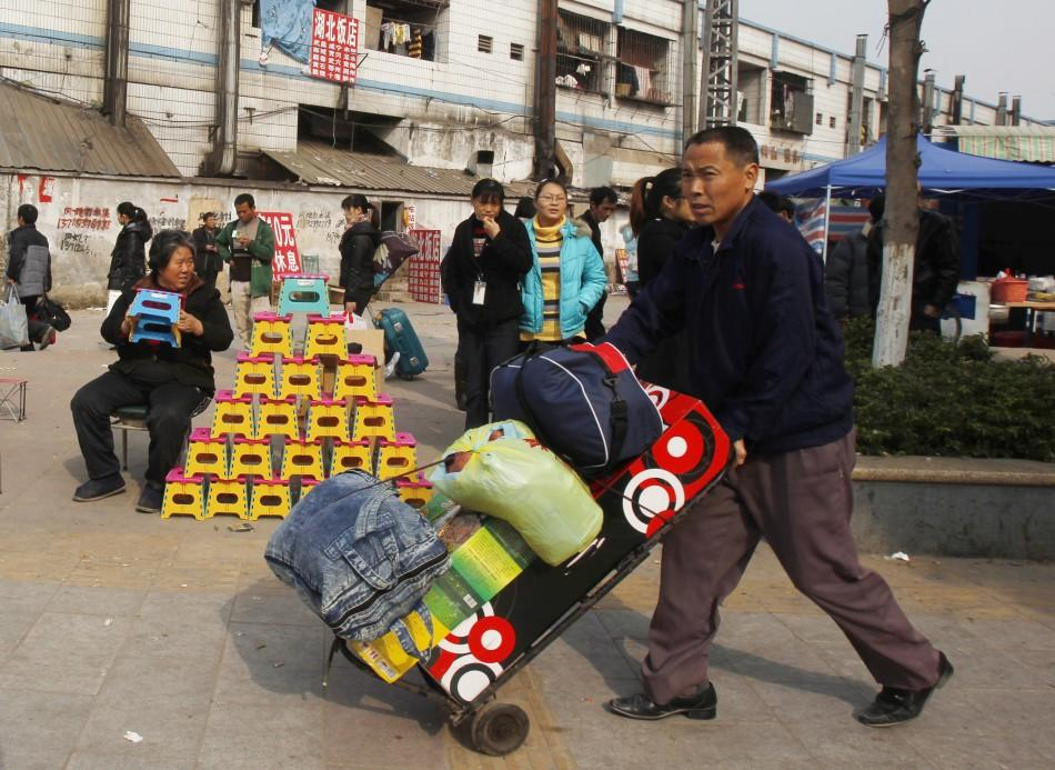 A migrant worker pushes his belongings past a vendor selling foldable stools near Dongguan East station in southern China