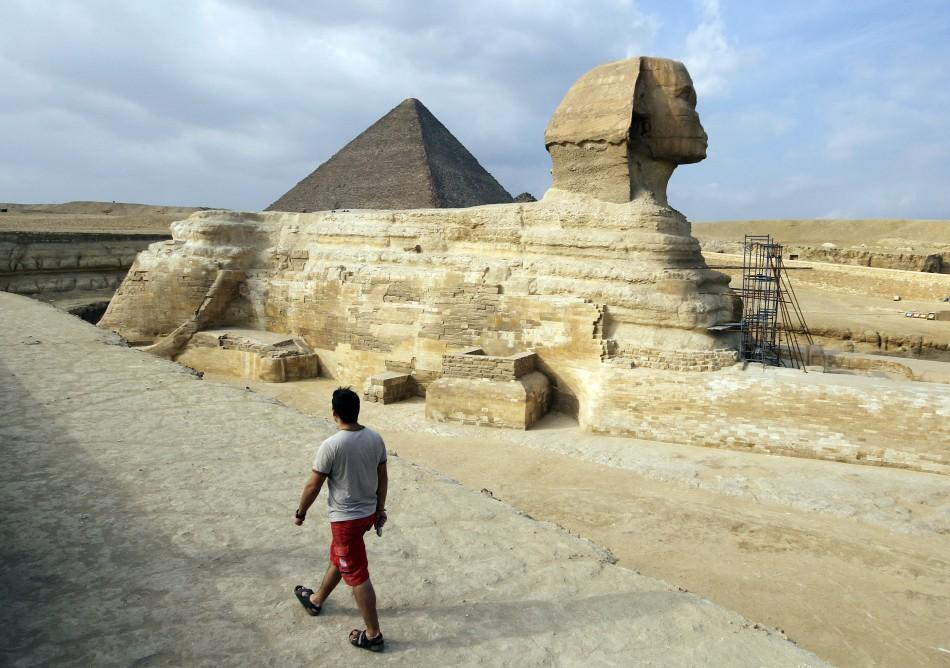 A tourist walks in front of the Great Giza pyramids on the outskirts of Cairo