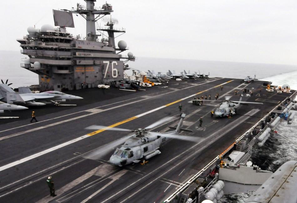 Helicopters on aircraft carrier prepare to deliver supplies