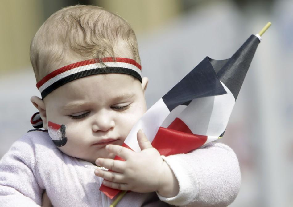 A baby holds an Egyptian flag at Tahrir Square in Cairo