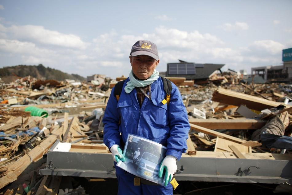 Shigemasa Kanno, 74, holds a photograph of his missing 68-year-old wife Sueko Kanno, at the debris of his destroyed house in Rikuzentakata