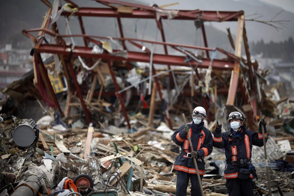 Japanese rescue workers pause from their operation in the destroyed residential part of Ofunato