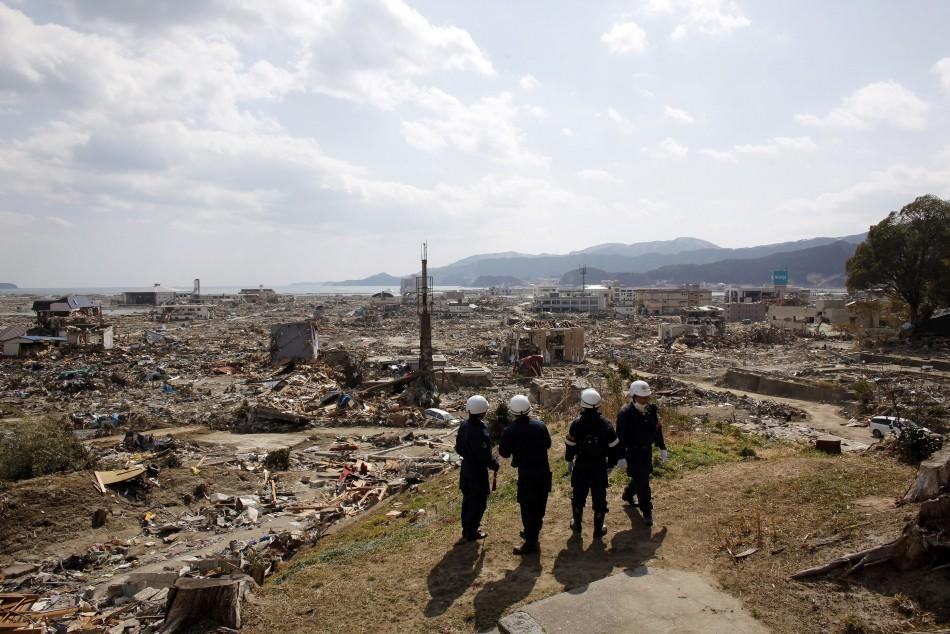 Emergency workers look out from the side of a hill near the debris area near the seaside in Rikuzentakata