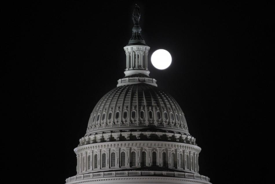 The full moon rises behind the U.S. Capitol Dome in Washington