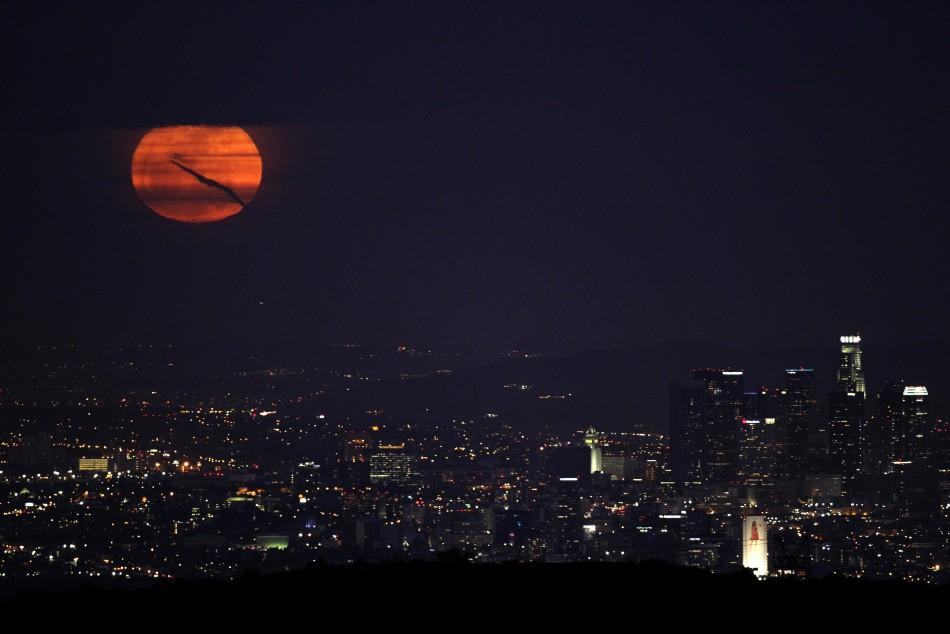 The moon rises over downtown Los Angeles