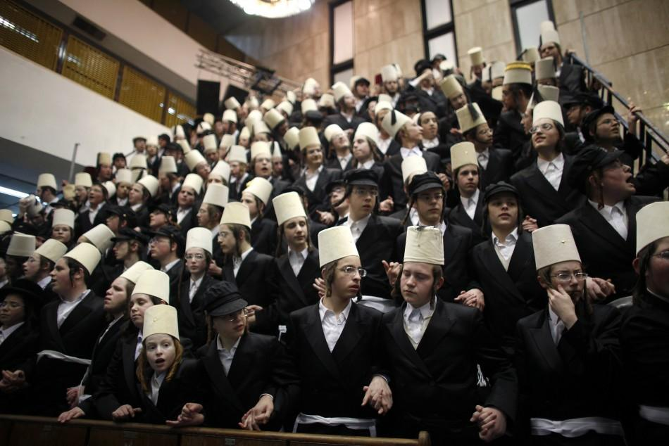 Ultra-Orthodox Jewish men dance while celebrating the Jewish holiday of Purim at a synagogue in Bnei Brak