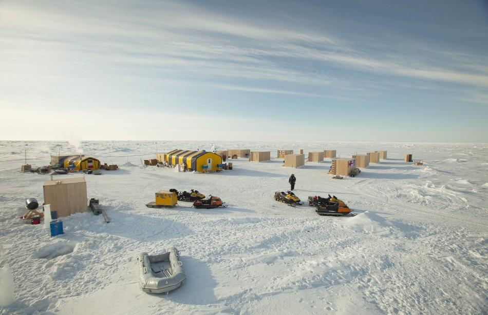 A man walks towards snow machines past the plywood hutches and tents that make up the Applied Physics Lab Ice Station in the Arctic north of Prudhoe Bay, Alaska