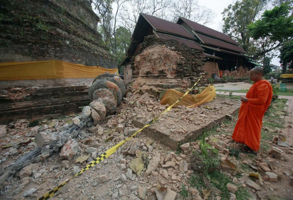 A Buddhist monk looks at a damaged pagoda after an earthquake at Wat Chedi Laung in Chiang Rai province