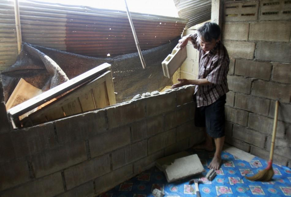 A villager clears his house after an earthquake in Chiang Rai province