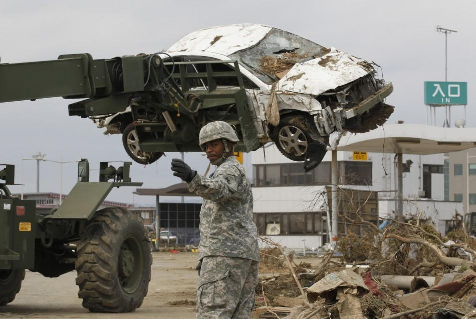 A U.S. marine based in Japan directs heavy lifting equipment as reconstruction work continues at Sendai airport