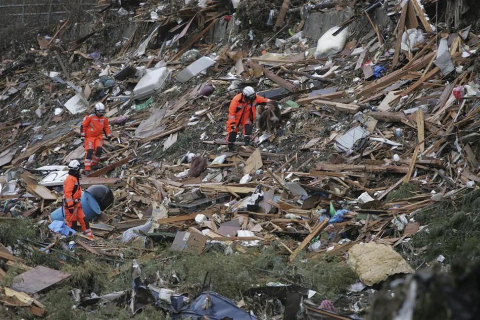 Members of Swiss Rescue team search through debris in Minamisanriku