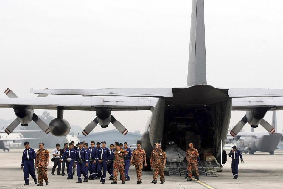 Members of the Special Malaysia Disaster Assistance and Rescue Team walk back to the terminal after loading supplies into an aircraft before leaving for earthquake and tsunami-hit Japan, at an airport in Subang