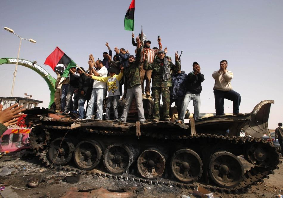People celebrate atop a destroyed tank belonging to forces loyal to Libyan leader Gaddafi after an air strike by coalition forces in Ajdabiyah