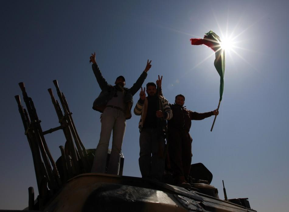 Rebel fighters celebrate on the outskirts of the town of Ajdabiyah
