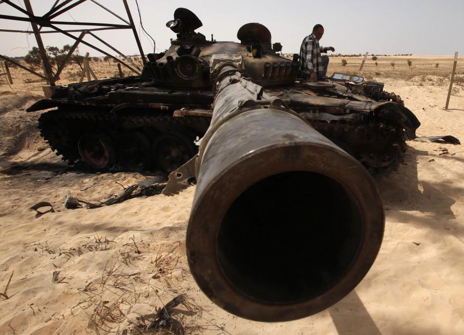 A man sits on the hull of a destroyed tank belonging to forces loyal to Libyan leader Gaddafi after an air strike by coalition forces in Ajdabiyah