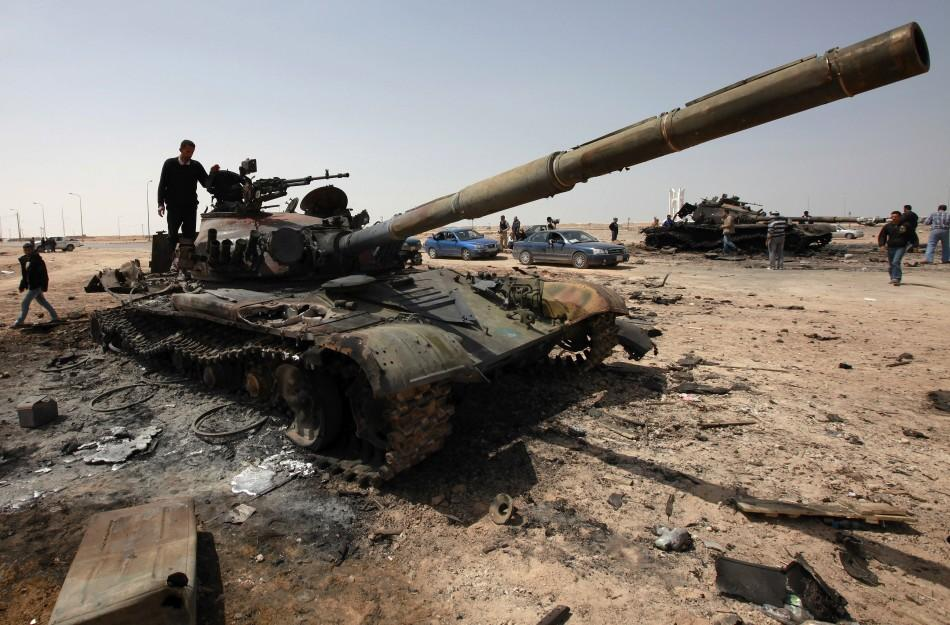 A man stands on a burnt tank on the western outskirts of the town of Ajdabiyah