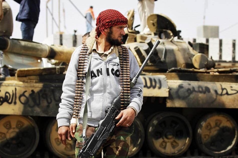 A rebel fighter stands by an abandoned tank after forces loyal to Muammar Gaddafi fled town following coalition air strikes around the eastern town of Ajdabiyah
