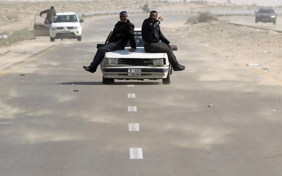 Rebel fighters ride on a car along the Benghazi-Ajdabiyah road near Ajdabiyah