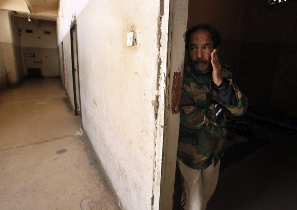 Suspected member of forces loyal to Libyan leader Muammar Gaddafi gestures inside a prison in Benghazi