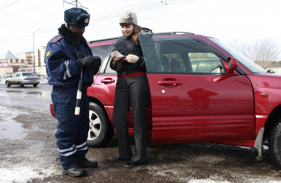 Samuel Brako from Ghana, a student of Krasnoyarsk University dressed as a road policeman, checks a driver's licence on a road in Russia's Siberian city of Krasnoyarsk