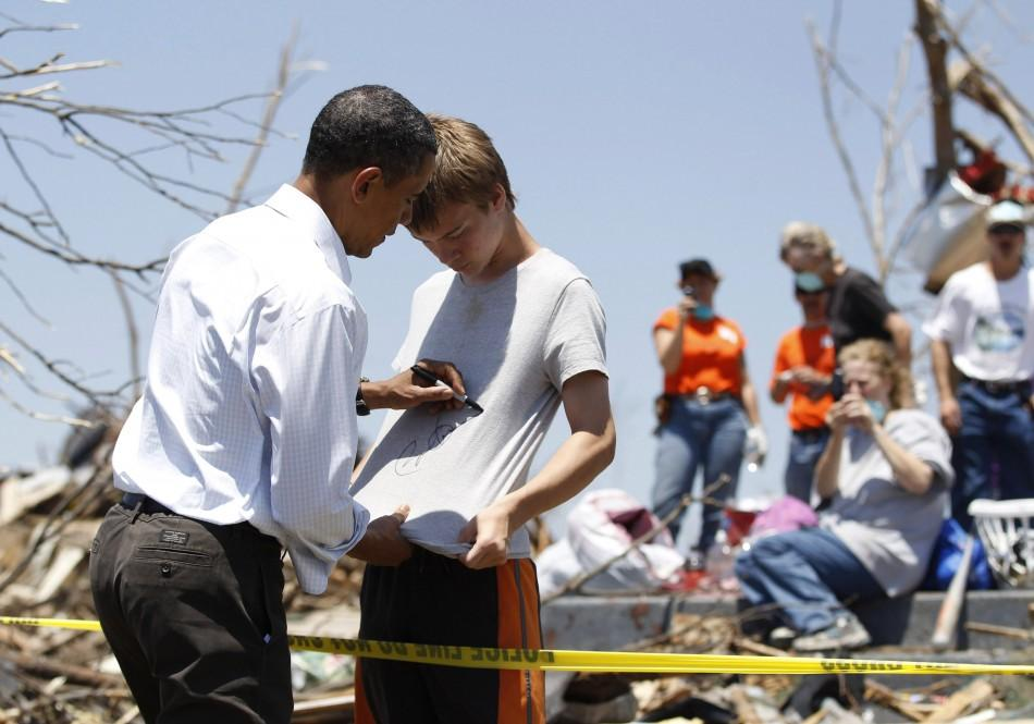 President Barack Obama autographs a boy's shirt