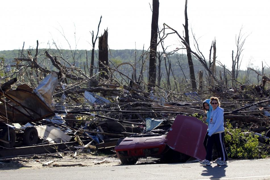 People walk by damage caused by a tornado in Brimfield