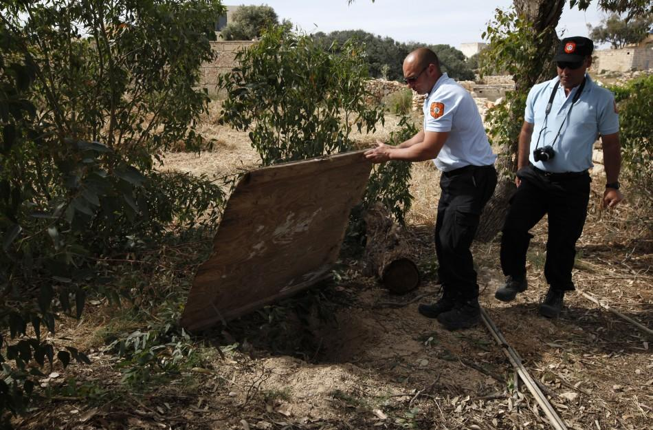 Animal welfare officers show the hole in the ground where they found a dog buried alive in a field near Birzebbuga in the south of Malta