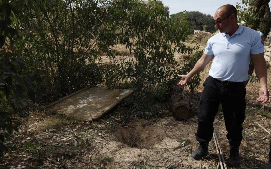 Animal welfare officer shows the hole in the ground where they found a dog buried alive in a field near Birzebbuga in the south of Malta