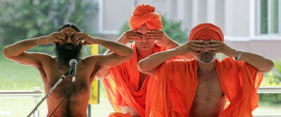 India's yoga guru Swami Ramdev and his followers perform yoga during his fast against corruption in Haridwar