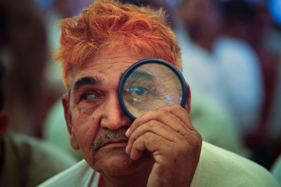 A supporter of India's yoga guru Ramdev uses a magnifying glass to watch his address at Ramlila grounds in New Delhi