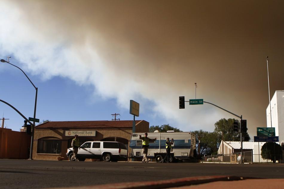 Police officers direct traffic as local residents evacuate from the Wallow Wildfire in Springerville, Arizona