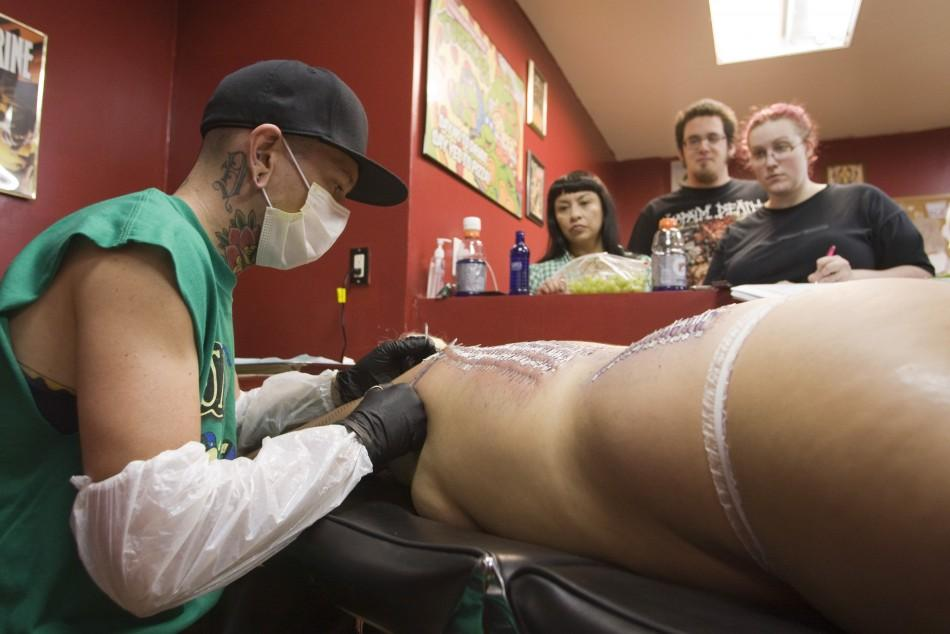 "Body piercer Bill ""Danger"" Robinson pierces the back of sideshow performer Staysha Randall during an attempt to break the Guinness Book record in Las Vegas"