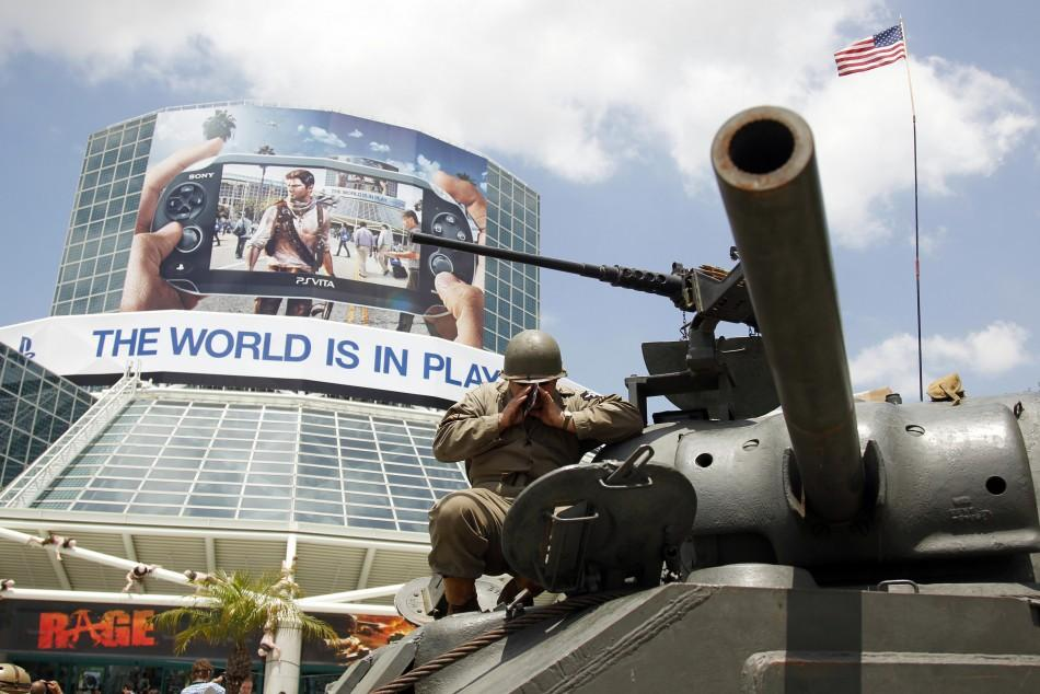 "A man yells into a World War II Sherman M4A3 military tank as they start the engine outside of the Los Angeles Convention Center during a promotion for the video game ""World of Tanks"" from British developer Wargaming.net during the Electronic En"