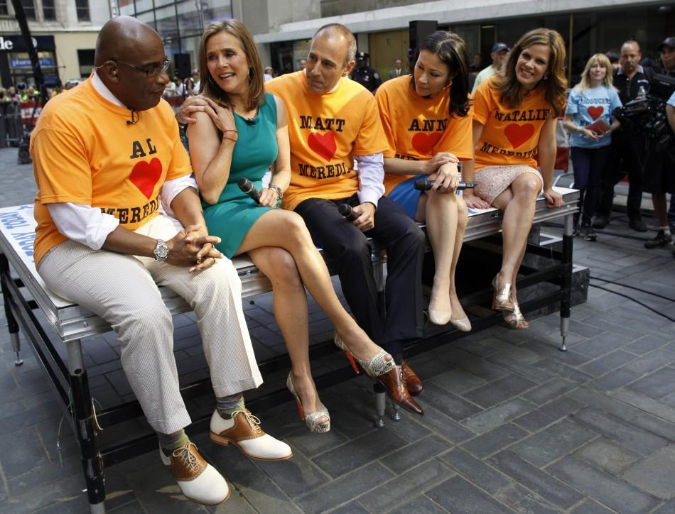 'Today' show host Meredith Vieira (C) pets her dog Jasper with Al Roker (L) and Matt Lauer (R) during her final show in New York, June 8, 2011. Vieira is leaving NBC's 'Today' show and will be replaced by the show's news anch