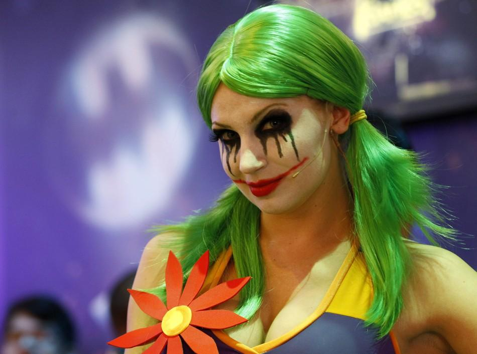 "A woman dressed as ""The Joker"" smiles for the camera while promoting Warner Bros. Interactive Entertainment, Inc.'s new video game ""Gotham City Impostors"" during the Electronic Entertainment Expo or E3 in Los Angeles"