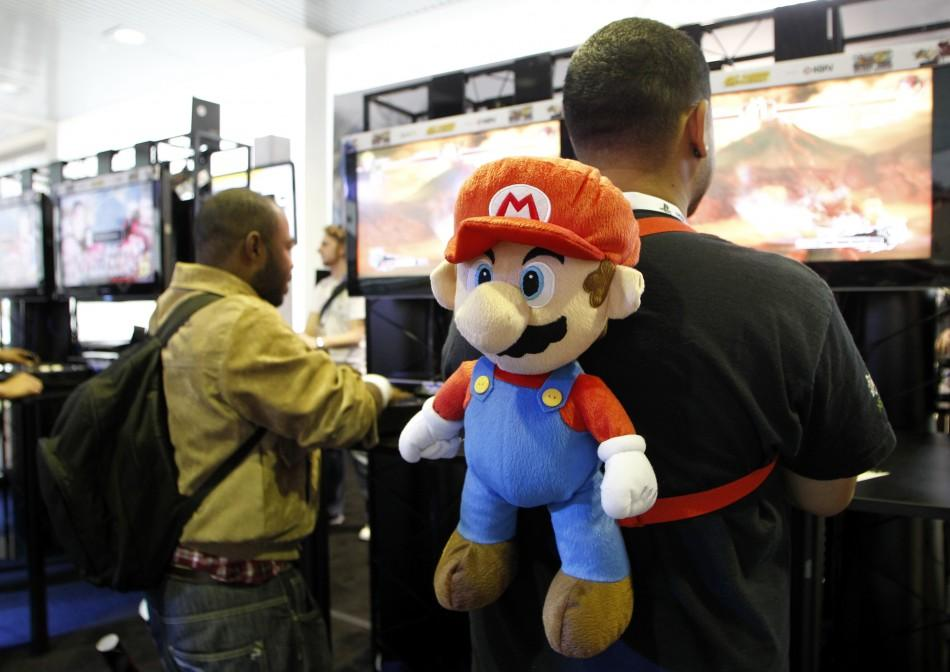 A gamer wears a Super Mario backpack as he plays a game during E3 in Los Angeles
