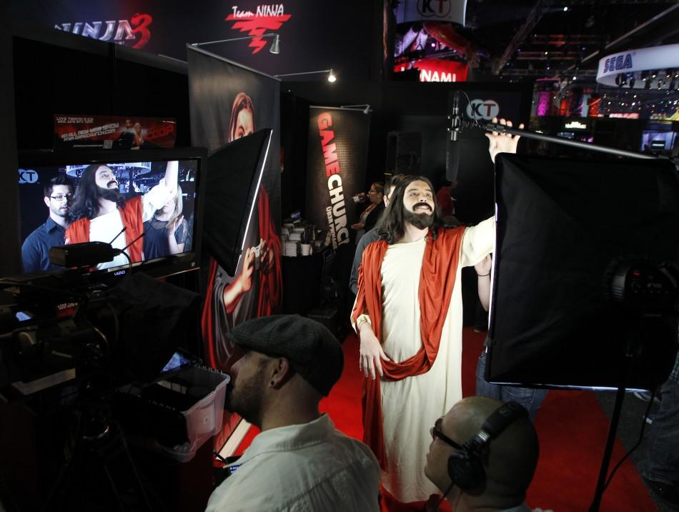 A man dressed as Jesus Christ grabs a microphone during a taping of a webisode for gaming website gamechurch.com during E3 in Los Angeles