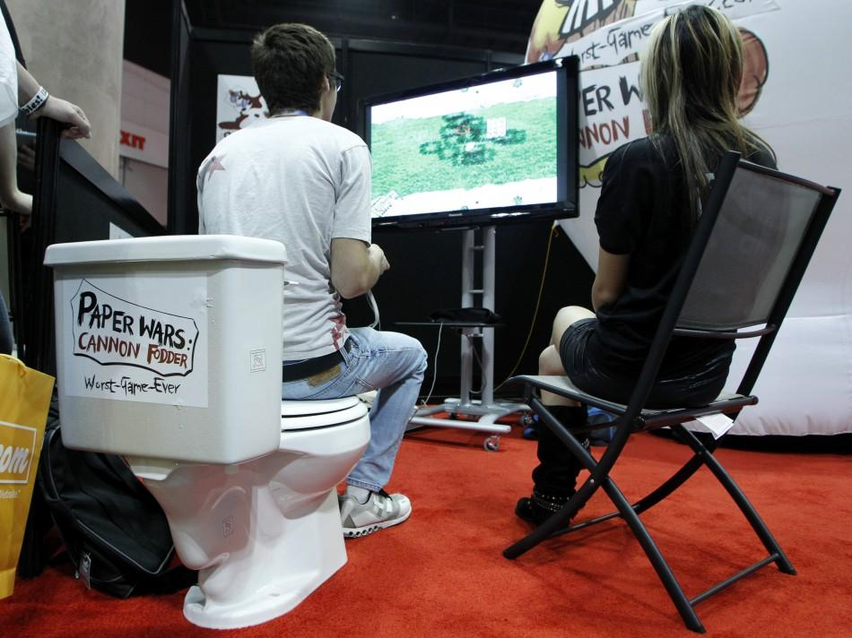 "A gamer sits on a toilet bowl as he plays the video game ""Paper Wars: Cannon Fodder"" by developer iFun4All during E3 in Los Angeles"