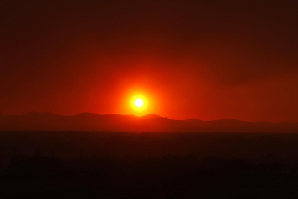 Smoke from the Wallow Wildfire billows over the White Mountains as the sun sets in Springerville