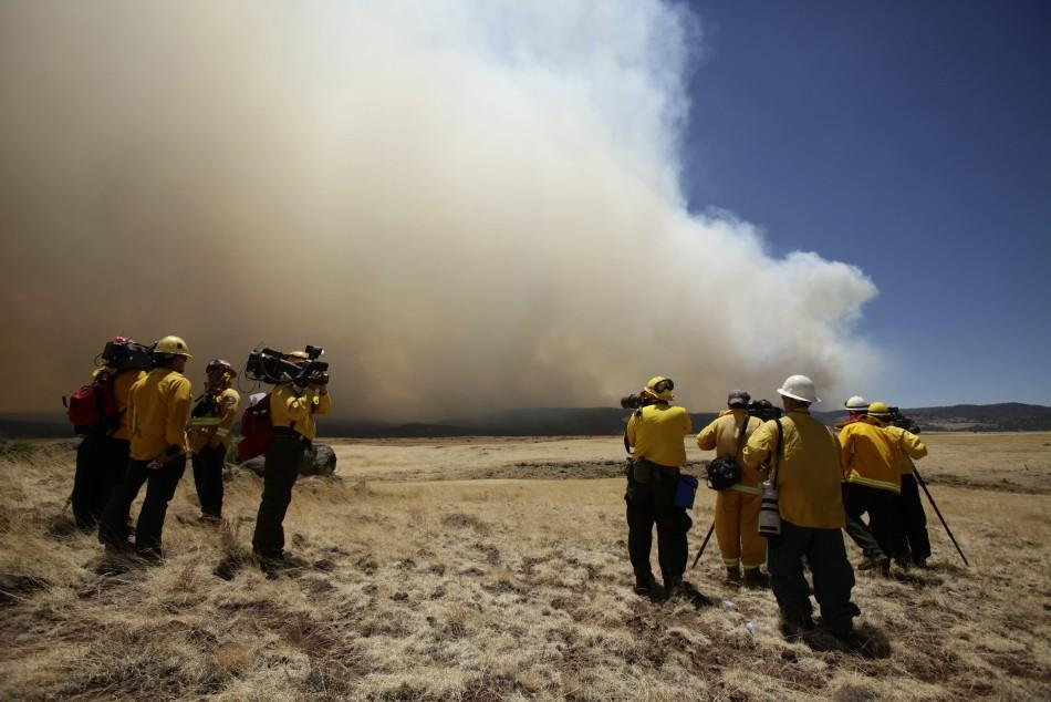 Reporters stand in a field as they watch smoke billowing over the White Mountains from the Wallow Wildfire in Apache County, Arizona