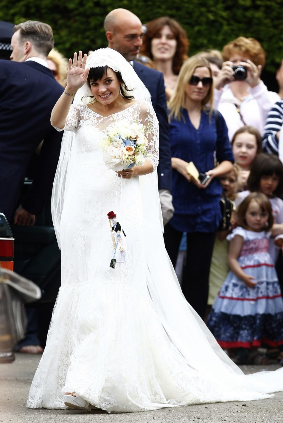 British Singer Allen waves after marrying Cooper as the couple leaves St James the Great Church in Cranham