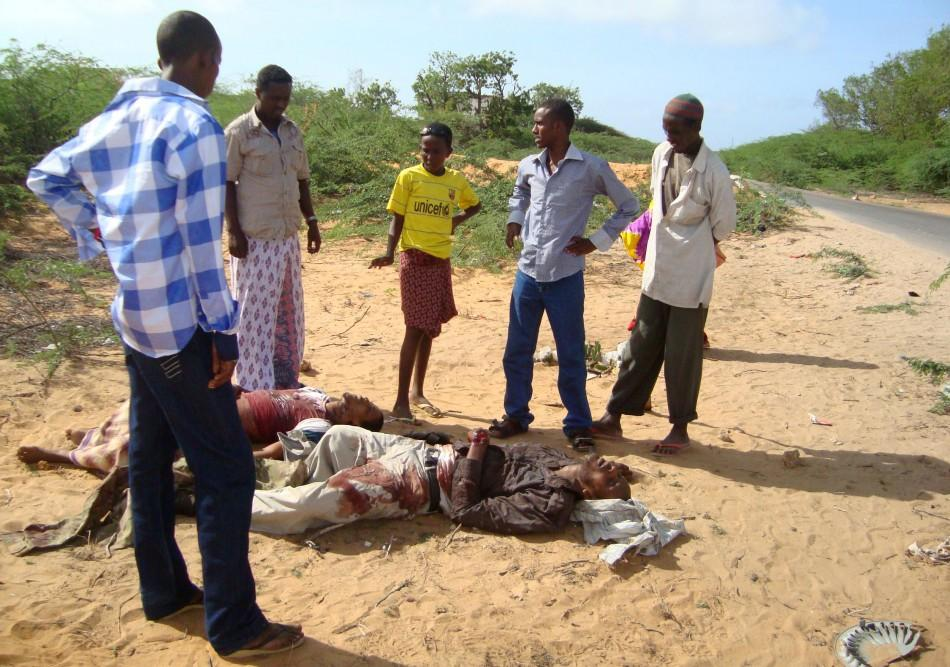 Civilians look at the suspected body of Fazul Abdullah and an unidentified colleague killed at a police checkpoint in Somalia's capital Mogadishu